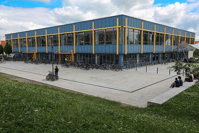 Ein blauer Mensa-Flachbau mit gelben Metallstreben an der Außenseite, davor ein weiträumiger, betonierter Platz